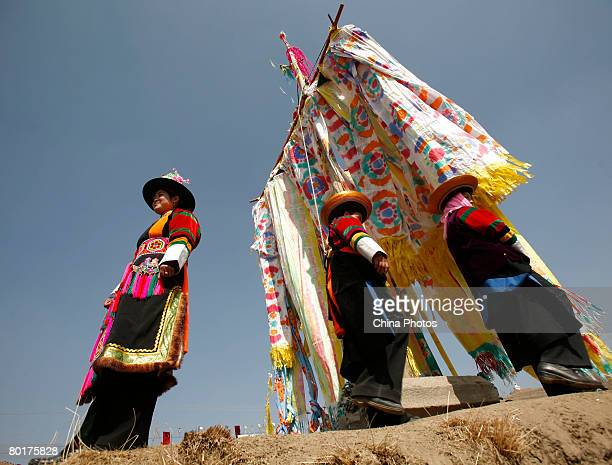 Villagers stand below Pray Flags during a ceremony to worship the Erlang God at the Dazhuang Village on March 9 2008 in Huzhu County of Qinghai...