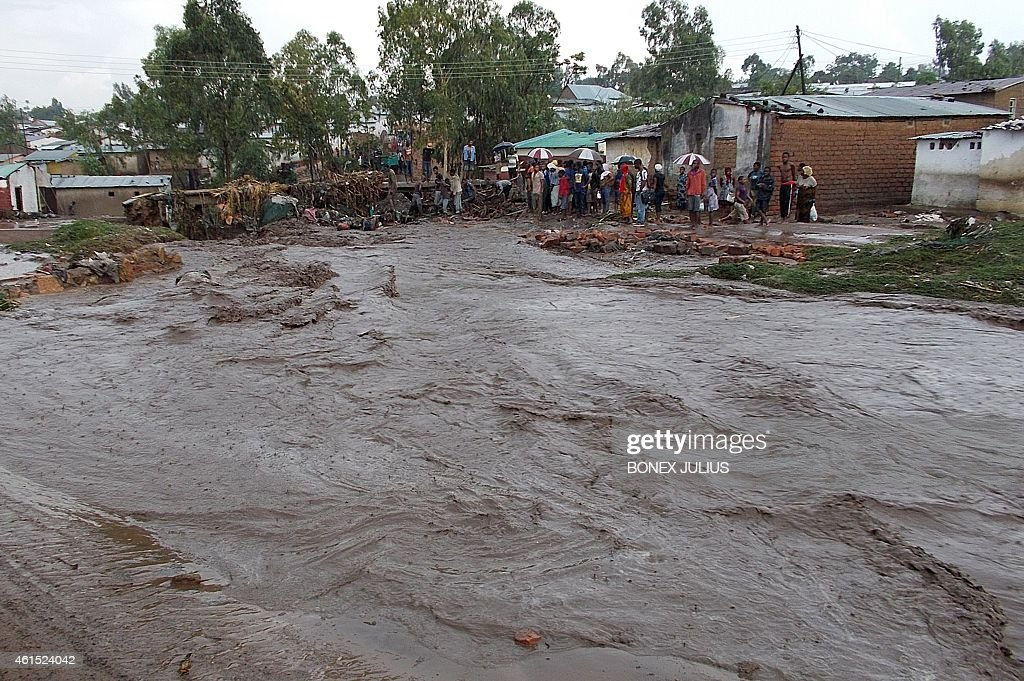 Villagers stand near a flooding street on January 12, 2015, in a township on the outskirts of Malawian capitol, Blantyre. Malawian President Peter Mutharika said Wednesday floods which have hit half of the country's 28 districts had killed 48 people, and appealed for international assistance. Nearly 70,000 people are now without homes, the country's president announced as he appealed for international assistance. JULIUS