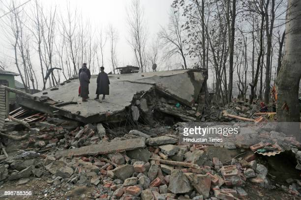 Villagers stand on the debris of a residential house which was destroyed during a gunfight at Samboora on December 26 2017 in Pulwama some 30...