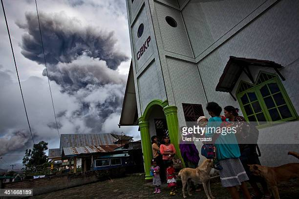 Villagers stand outside a church as following another eruption of Mount Sinabung at Simpang Empat village on November 24 2013 in Karo district North...