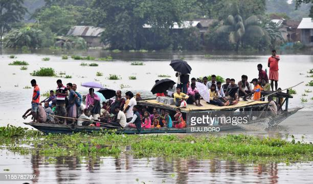 Villagers travel on a boat in the flood affected Jhargaon village in Morigaon district of India's Assam state on July 15, 2019. - Floods and...