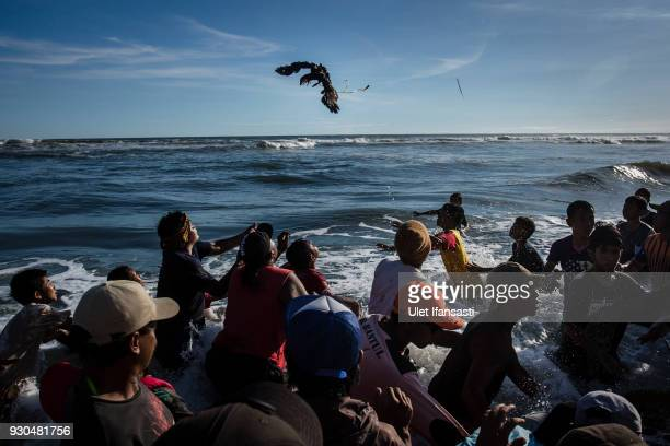 Villagers trying to catch a chicken after being thrown by Hindu worshippers as an offering during the Melasti ritual ceremony at Parangkusumo beach...