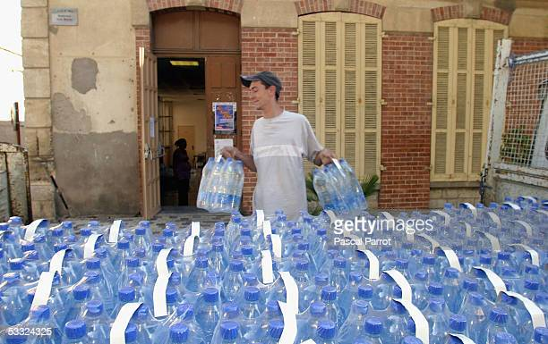 Villagers unload bottles of water from the local council on August 4 2005 in Flayosc France Flayosc has a population of 8000 people and currently has...