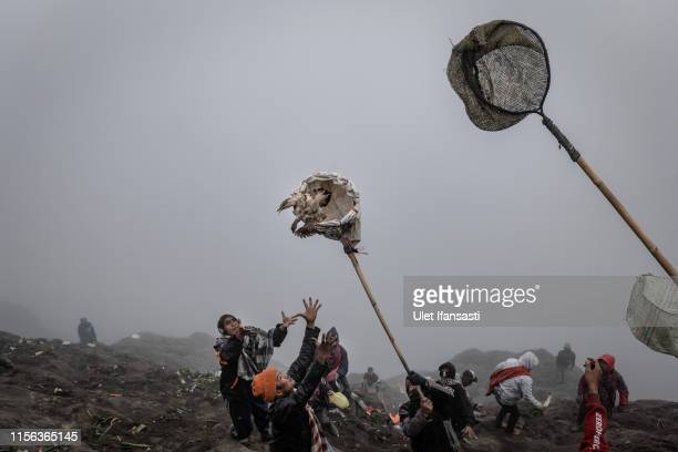 Villagers use a net to catch chickens thrown as offerings by Tenggerese worshippers during the Yadnya Kasada Festival at crater of Mount Bromo on...