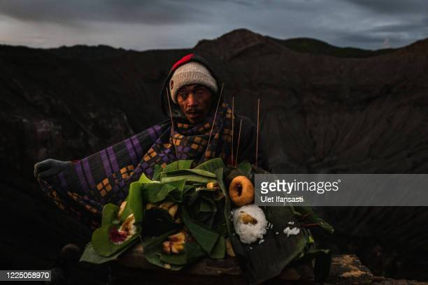 Villagers use a sarong to catch offering thrown by Tenggerese worshippers during the Yadnya Kasada Festival at crater of Mount Bromo amid the...