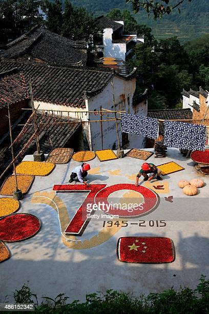 Villagers use dried red chilli peppers white kidney beans rice buckwheat and adzuki beans to create a pattern to celebrate the 70th anniversary of...