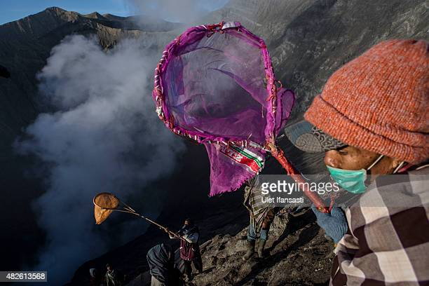 Villagers use nets and sarongs as they waits to catch offerings thrown by Hindu worshippers during the Yadnya Kasada Festival at crater of Mount...