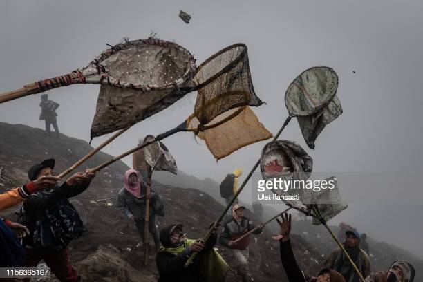 Villagers use nets to catch money thrown as an offering by Tenggerese worshippers during the Yadnya Kasada Festival at crater of Mount Bromo on July...