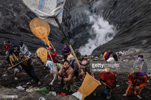 Villagers use nets to catch offering thrown by Tenggerese worshippers during the Yadnya Kasada Festival at crater of Mount Bromo amid the coronavirus...