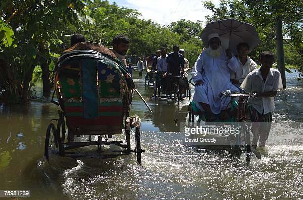 Villagers use rickshaws to pass through rising floodwaters on August 6 2007 outside of Srinigar Bangladesh about 30km south of Dhaka While water...