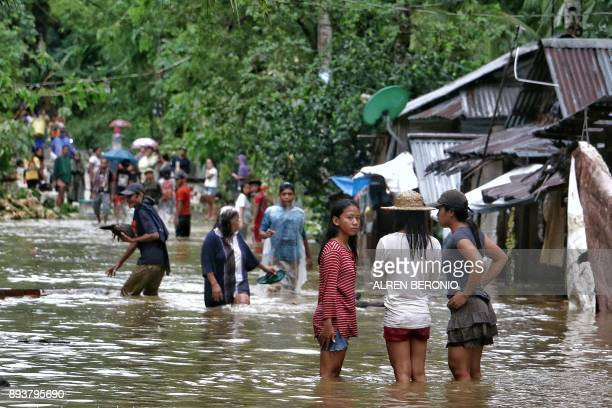 TOPSHOT Villagers wade through a flooded street in Brgy Calingatngan in Borongan on easterm Samar in central Philippines on December 16 2017 A boy...
