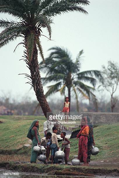 Villagers wait in hope that emergency relief will arrive in their village near Chittagong Food and other supplies were being dropped from helicopters...