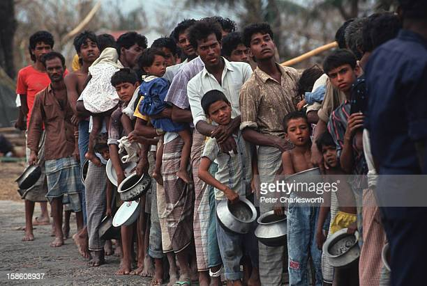 Villagers wait in in line for emergency relief that has finally arrived in Chittagong Food and other supplies were being dropped from helicopters to...