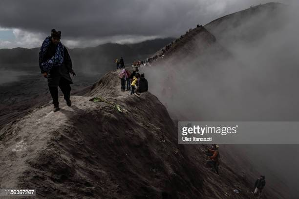 Villagers waits to catch offerings thrown by Tenggerese worshippers during the Yadnya Kasada Festival at crater of Mount Bromo on July 18 2019 in...