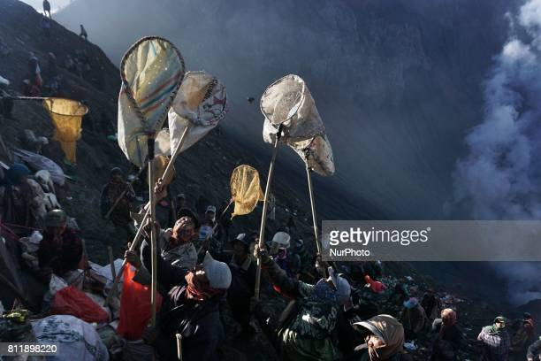 Villagers waits to catch the offerings thrown by Tenggerese worshippers during the Yadnya Kasada Festival at crater of Mount Bromo in Probolinggo...