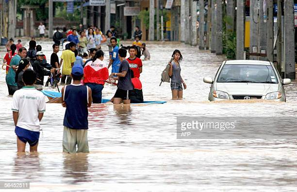 Villagers walk in flood water on the main road of Hat Yai city 18 December 2005 The death toll from floods across southern Thailand since November...