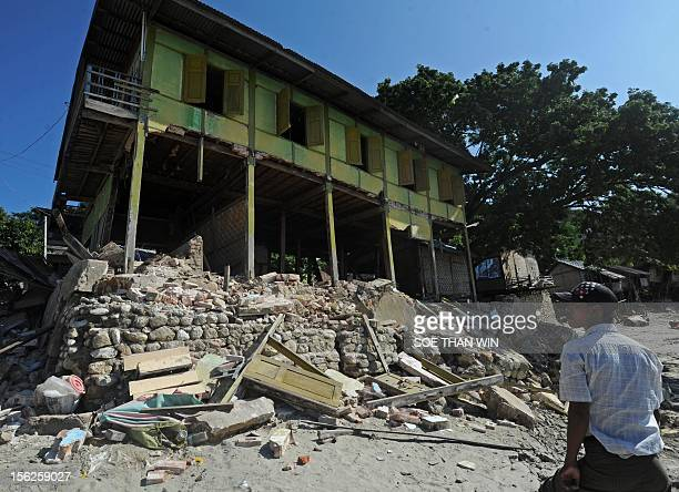 Villagers walk past an earthquake damaged house in Thabeik Kyin township Mandalay a division in central Myanmar on November 12 2012 Rescuers in...