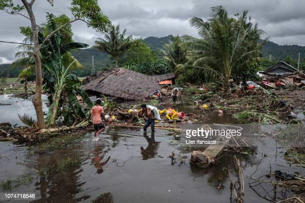 Villagers walk through debris after hit by tsunami as they carry their belonging on December 24 2018 in Carita Banten province Indonesia Over 280...