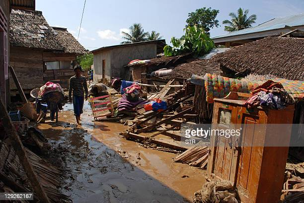 Villagers walk through mud as they salvage belongings following flash floods in the village of Desa Bhuvu in Donggala Sulawesi on October 15 2011...