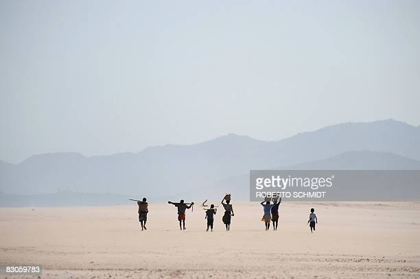 Villagers walkson a stretch of beach next to a fresh water reservoir near the village of Ambinanibe in the vicinity of the southern coastal town of...