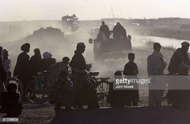 Villagers watch as a convoy of the Afghan Eradication Force returns to base after plowing opium poppy fields on April 3, 2006 near Lashkar Gah in the...