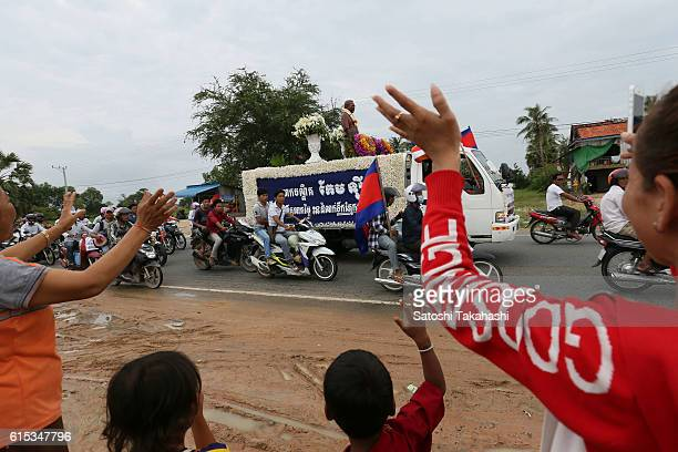 Villagers wave their hands to a funeral procession for slain prominent political analyst Kem Ley to mark 100 days since his death Kem Ley was shot...