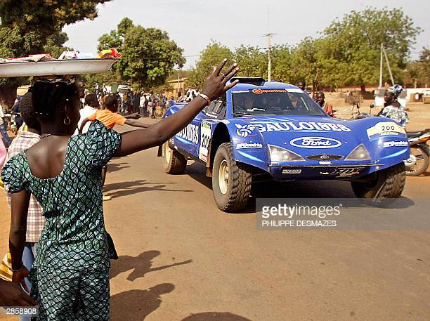 Villagers wave to French Dakar rally competitor JeanLouis Schlesser 11 January 2004 in Bougouni as all the competitor reach BoboDioulasso where the...