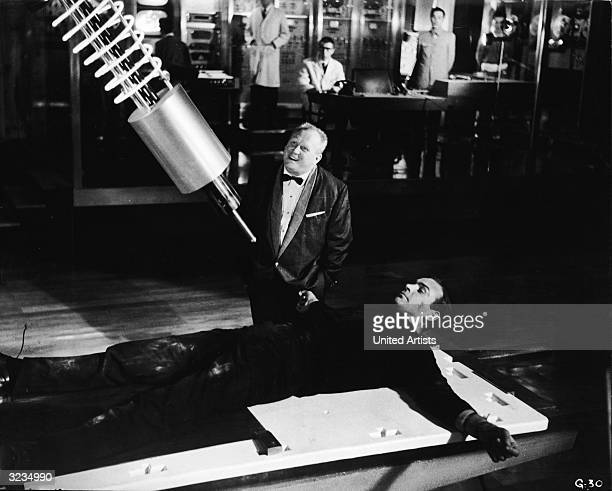 Villain Auric Goldfinger laughs as British agent James Bond lies strapped to a table beneath a laser weapon in a still from the film, 'Goldfinger,'...