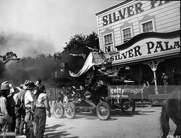 Villains Jack Lemmon and Peter Falk stand atop their Hannibal Eight automobile on a raised chassis leaving a cloud of black smoke as they enter a...