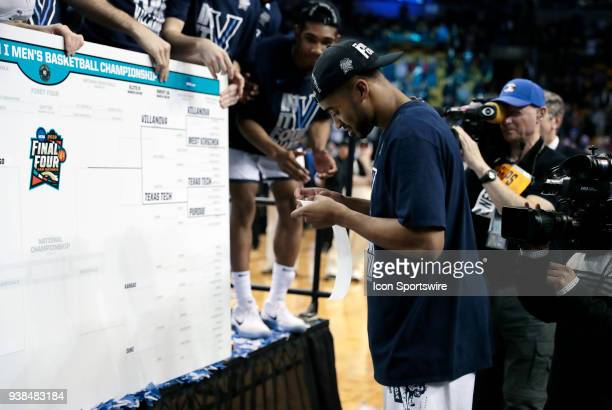 Villanova guard Phil Booth prepares to place the Villanova sticker on the bracket during an Elite Eight matchup between the Villanova Wildcats and...