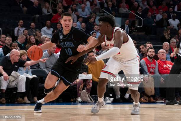 Villanova Wildcats Forward Cole Swider dribbles the ball along the baseline with St. John's Red Storm Forward Marcellus Earlington defending during...