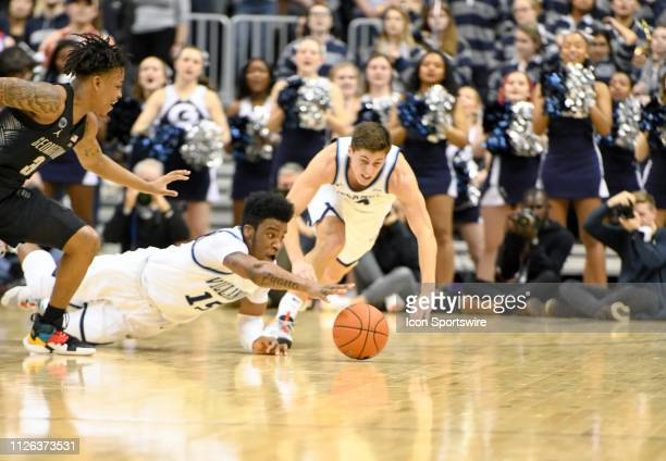 Villanova Wildcats forward Saddiq Bey dives for a loose ball with Georgetown Hoyas guard James Akinjo on February 20 at the Capital One Arena in...