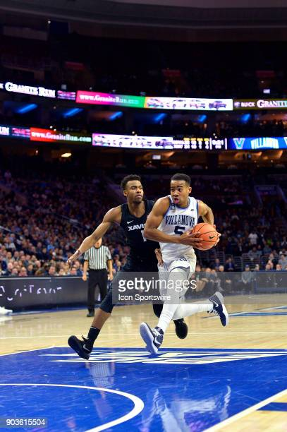 Villanova Wildcats guard Phil Booth charges into the lane synchronized with Xavier Musketeers guard Paul Scruggs during the basketball game between...