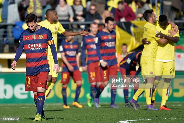 Villarreal players celebrate their second goal as Barcelona's Argentinian forward Lionel Messi walks away during the Spanish league football match...