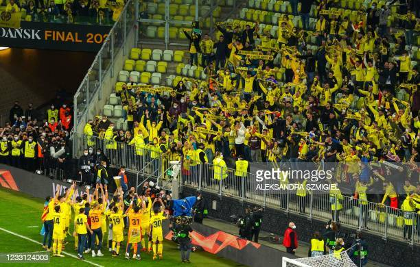 Villarreal players hold up their trophy in front of fans as they celebrate winning the 2021 UEFA Europa League football final between Spain's...