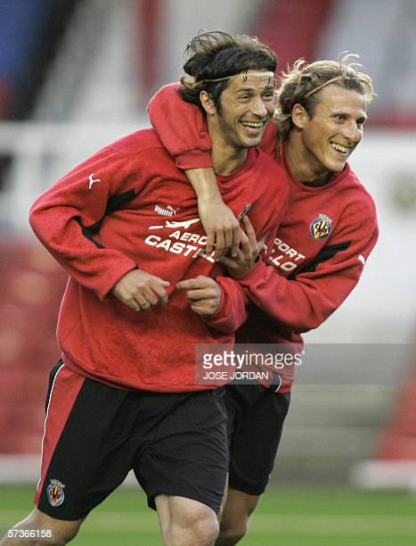 Villarreal 's Uruguayan Diego Forlan jokes with Italian Alessio Tacchinardi during a training session on the eve of their Champions League match...