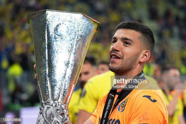 Villarreal's Argentine goalkeeper Geronimo Rulli celebrates with the trophy after winning the UEFA Europa League final football match between...