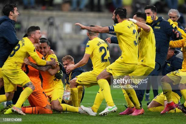 Villarreal's Argentine goalkeeper Geronimo Rulli is congratulated by teammates after stopping a penalty in a shoot-out during the UEFA Europa League...