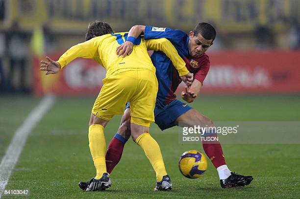 Villarreal's Cani fights for the ball with Barcelona 's Brazilian player Daniel Alves during their Spanish league football match at Madrigal Stadium...