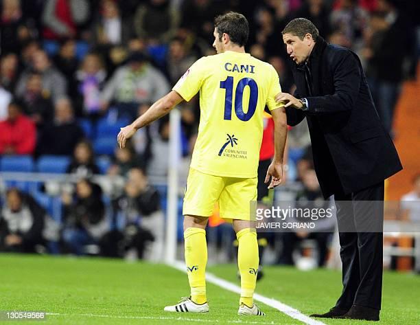 Villarreal's coach Juan Carlos Garrido speaks with Villarreal's midfielder Cani during the Spanish League football match Real Madrid against...