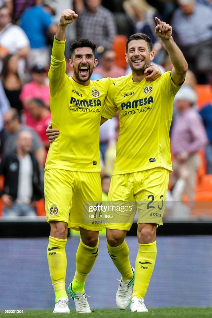 Villarreal's defender Alvaro Gonzalez (L) and Villarreal's Italian defender Daniele Bonera celebrate at the end of the Spanish League football match Valencia CF vs Villarreal CF at the Mestalla stadium in Valencia on May 21, 2017. /