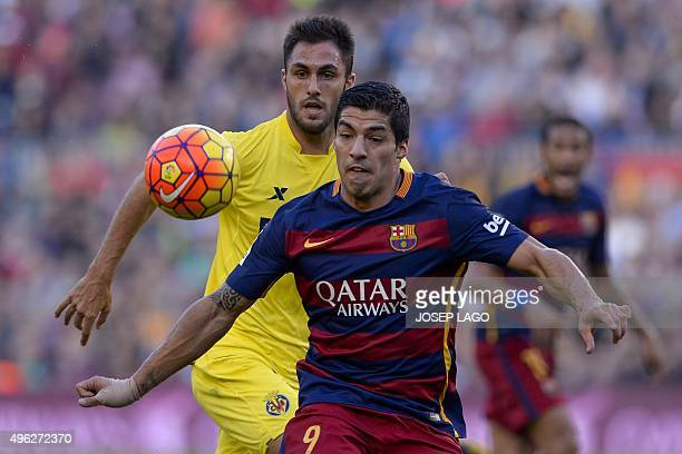 Villarreal's defender Victor Ruiz vies with Barcelona's Uruguayan forward Luis Suarez during the Spanish league football match FC Barcelona vs...