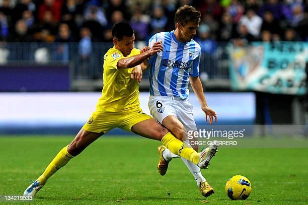 Villarreal's Dutch midfielder Hernan Perez vies for the ball with Malaga's midfielder Ignacio Camacho during the Spanish league football match Malaga...