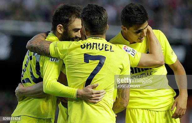 Villarreal's forward Adrian Lopez celebrates his second goal with teammates during the Spanish league football match Valencia CF vs Villarreal CF at...