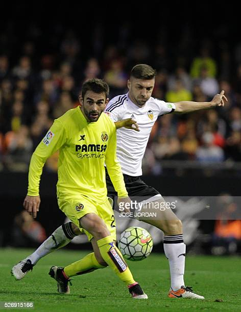Villarreal's forward Adrian Lopez vies with Valencia's Brazilian defender Guillerme Siqueira during the Spanish league football match Valencia CF vs...