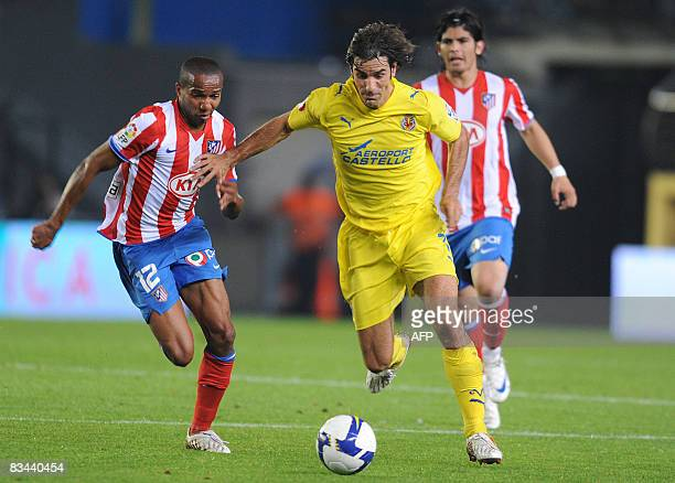 Villarreal's French Robert Pires fights for the ball with Atletico Madrid's Brazilian Assuncao during their Spanish league football match at the...