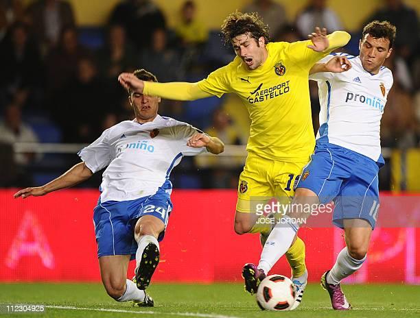 Villarreal's midfielder Cani vies for the ball with Zaragoza's Argentinian midfielder Nicolas Bertolo and Zaragoza's Serbian defender Ivan Obradovic...