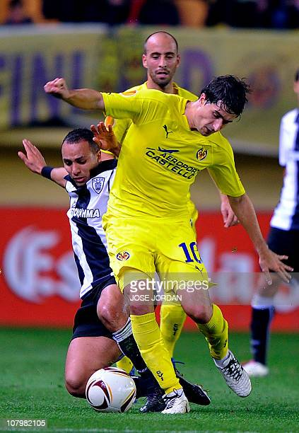 Villarreal's midfielder Cani vies with Paok Salonica Nabil El Zhar from Morocco during their UEFA Europa League football match on October 21, 2010 at...