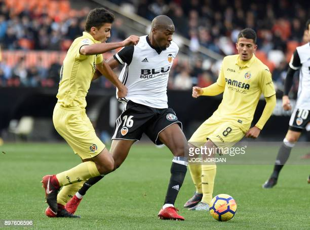 Villarreal's midfielder Pablo Fornals and Villarreal's midfielder Rodrigo Hernandez vie with Valencia's French midfielder Geofrey Kondogbia during...