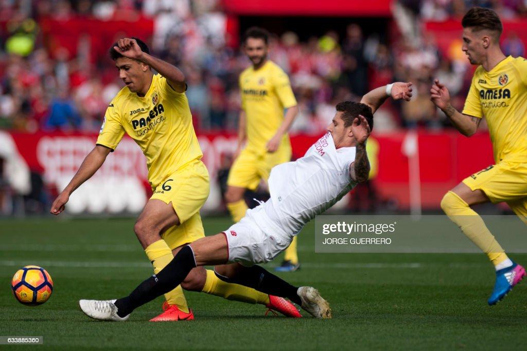 Villarreal's midfielder Rodrigo Hernandez (L) vies with Sevilla's Montenegrin forward Stevan Jovetic (C) during the Spanish league football match Sevilla FC vs Villarreal CF at the Ramon Sanchez Pizjuan stadium in Sevilla on February 5, 2017. / AFP / JORGE